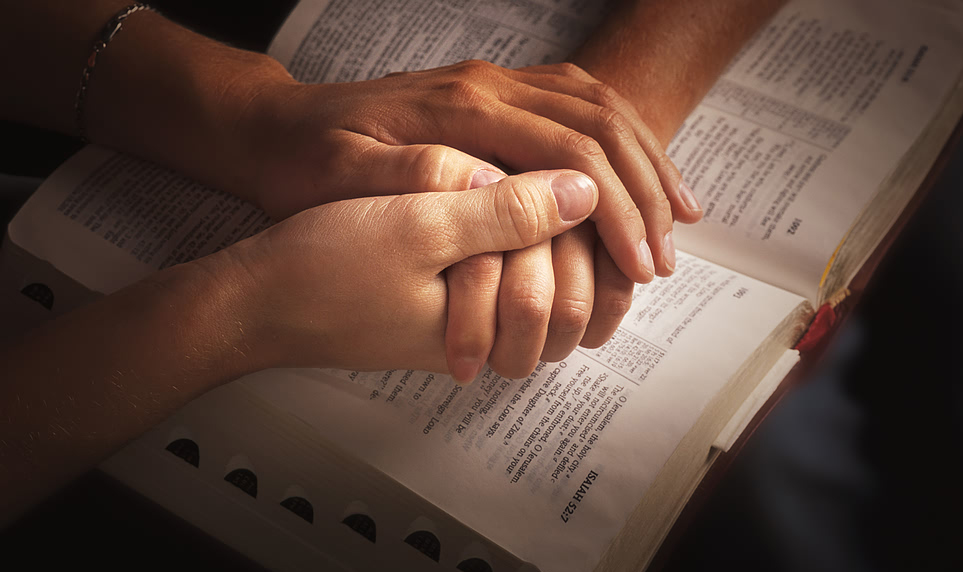 Two people holding hands over a Bible